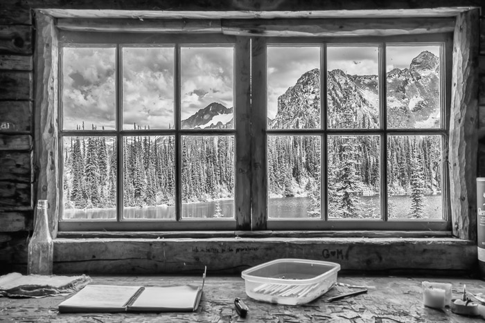 An icy landscape photographed through a cabin window. Natural framing for landscape photography composition