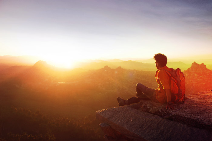 A photo of a backpacker sitting on the edge of a cliff looking toward the sunset. Tips for Light Meter Photography