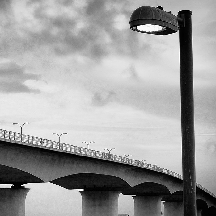 Black and white minimal photography of a bridge with a streetlamp in the foreground