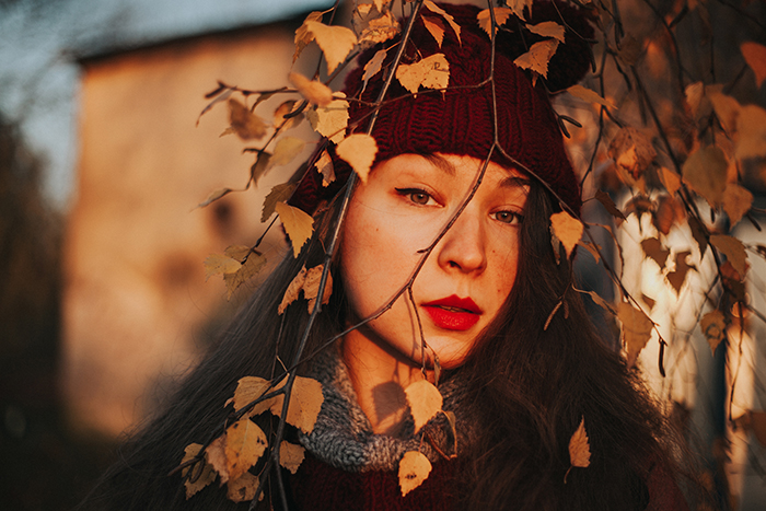 natural light portrait of girl in red hat looking out through autumn trees