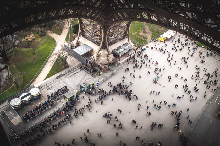 Travel photograph from the first floor of the Eiffel tower, looking down on many tourists below.