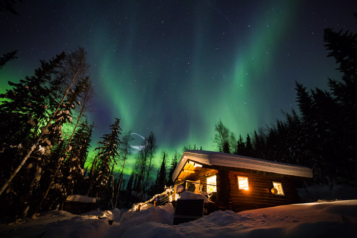 Beautiful view of the northern lights over a wooden cabin in the forest north of Fairbanks, Alaska
