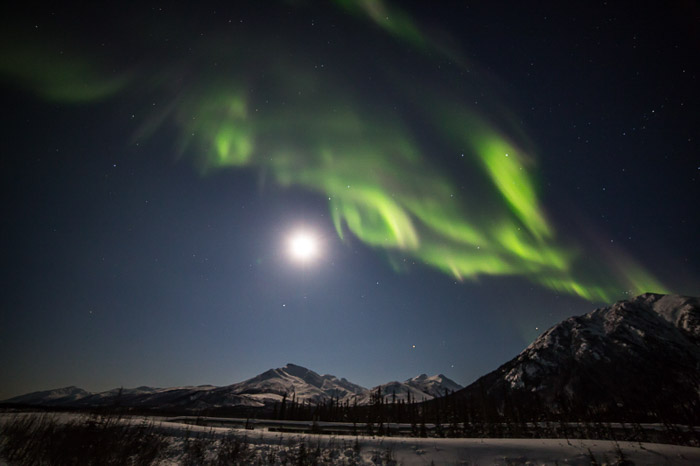 Photo of the moon lighting up the Brooks Range of northern Alaska in warm light with the aurora borealis above.