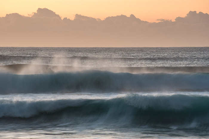 Blurred waves seascape with orange and yellow sky. Ocean photography
