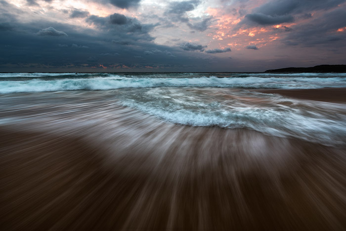 Impressive reducing wave seascape with fiery sunset sky using shutter speed of 0.5 - 2 seconds. Ocean photography
