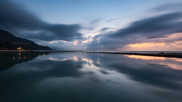 Calm evening seascape with sunset sky and mountains reflected in the sea. Ocean photography