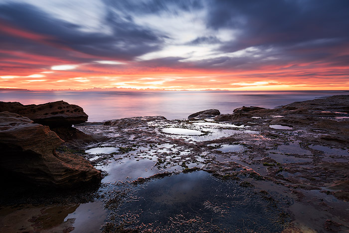 A dramatically lit rock pool seascape with fiery sunset. Ocean photography