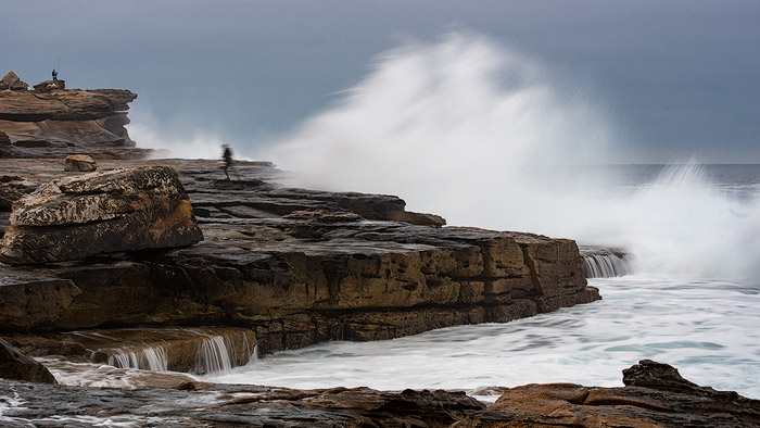 Seascape photo of a two people fishing on the rocks with large waves behind.