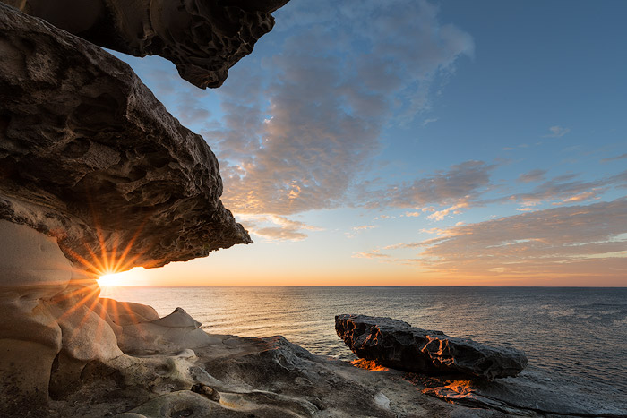 Blended sunburst seascape photo with rocks and cloudy blue sky. Ocean photography