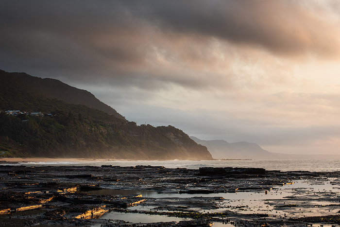 Calm evening seascape with overcast sky and mountains. Ocean photography