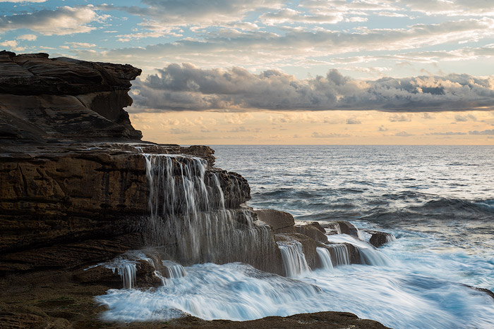 Seascape photo of a waterfall running into the ocean, cloudy skies.
