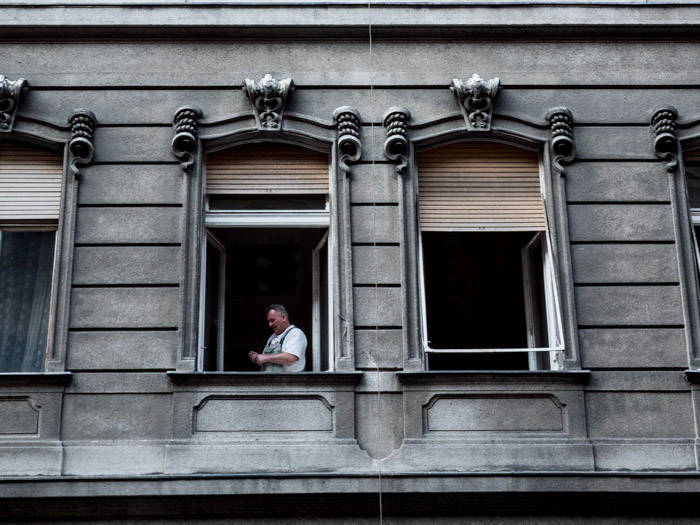 Street photography of open windows of a building, a man standing inside one, taken with a Panasonic gh5 by Craig Hull