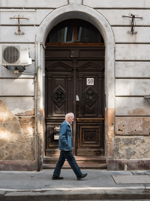 Street photography of a man walking past a doorway in Budapest, taken with a Panasonic gh5 by Craig Hull