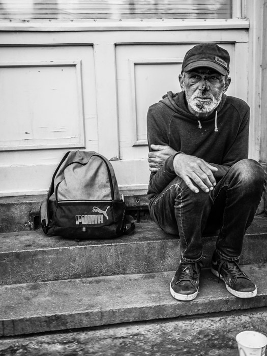 Black and white street photography of a homeless man sitting on a step in Budapest, taken with a Panasonic gh5 by Craig Hull