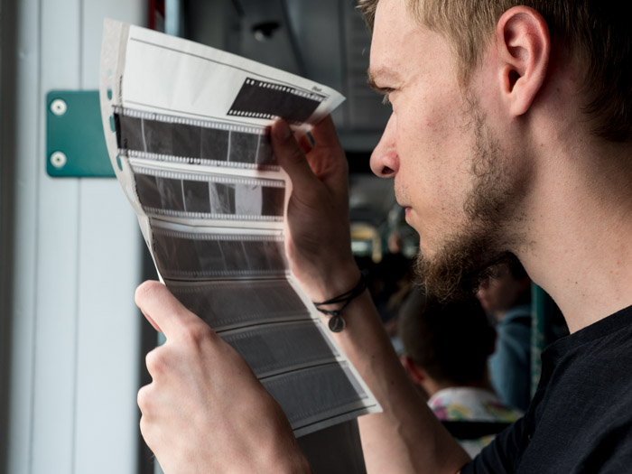 Street photography of a man looking at film negatives, taken with a Panasonic gh5 by Craig Hull