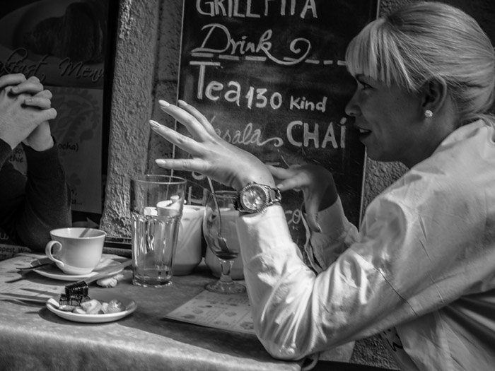 Black and white street photography of people chatting at a cafe table, taken with a Panasonic gh5 by Craig Hull