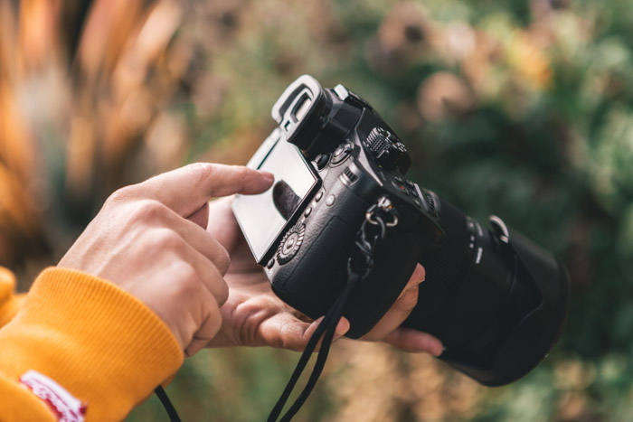 Close up of a persons hands holding a panasonic gh5 outdoors