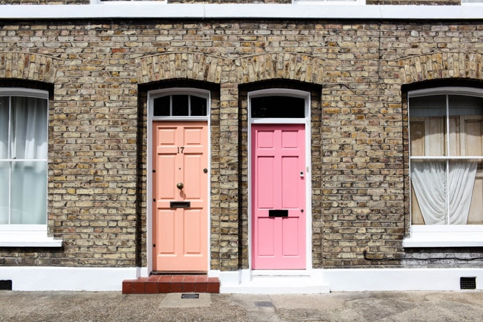 Street photography of 2 pink front doors of brick houses.