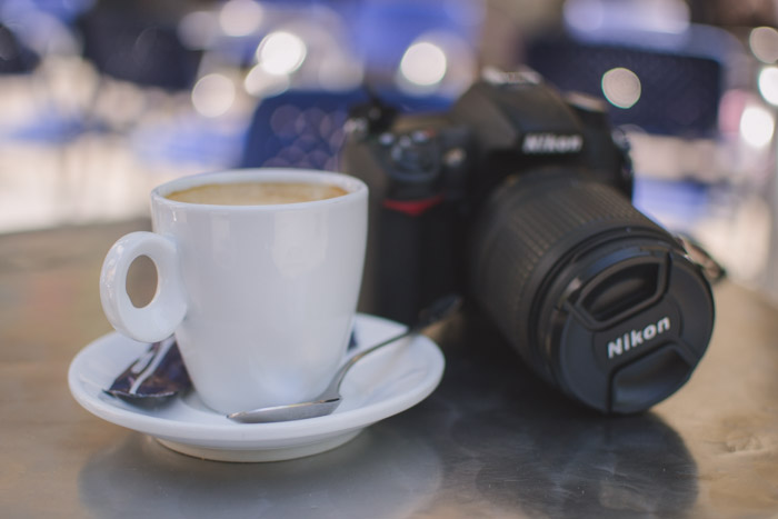 Blurry photo of a Nikon camera and white coffee cup resting on a table - enjoy your time on your photo walk!