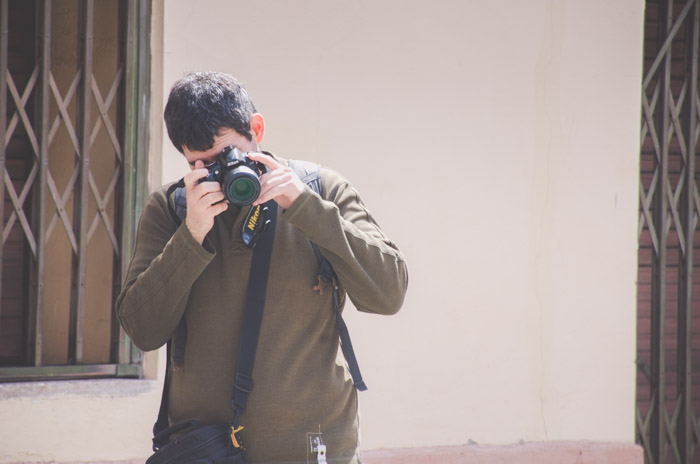 Photo of a man in dark green jumper taking a photo with a Nikon SLR camera during a photo walk