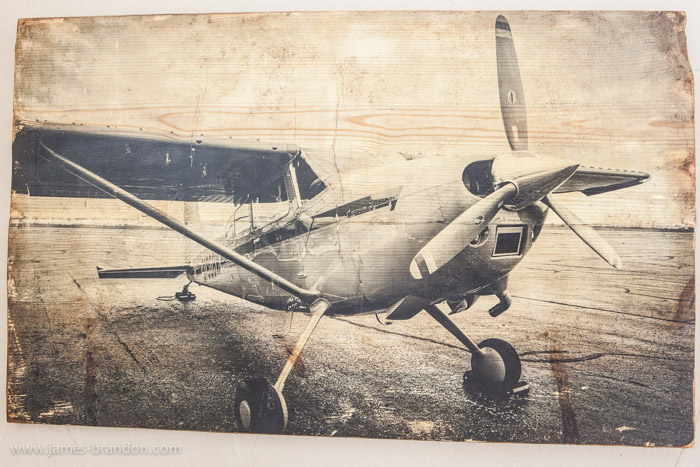 A black and white photo of an airplane on wood - photo gifts - https://digital-photography-school.com/how-to-transfer-prints-to-wood-an-awesome-photography-diy-project/