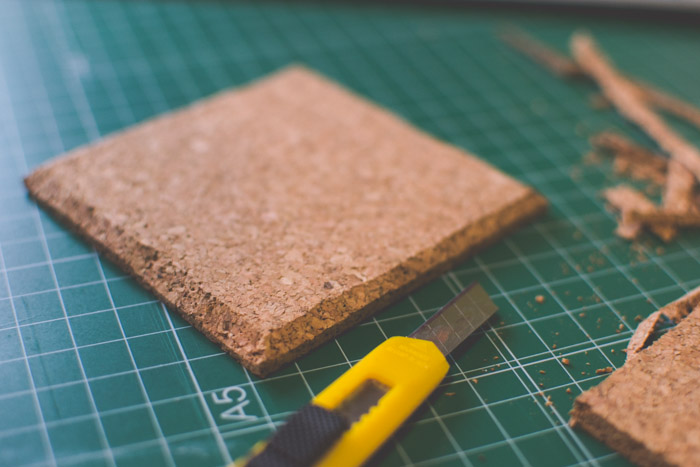 A close up of a coaster being trimmed on a cutting mat. Creative photography ideas.