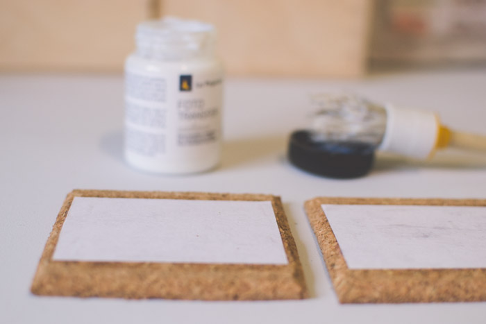 A close up photo of gluing photographs to coasters. Creative photography ideas.