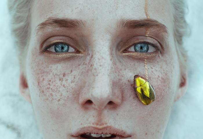 Ciro Galluccio creative close up portrait of a female with a golden beetle on her cheek. Famous Portrait Photographers