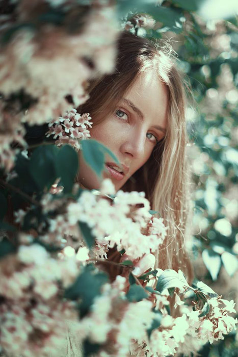 Federico Sciuca cinematic portrait of a girl looking out through flowers. Famous Portrait Photographers