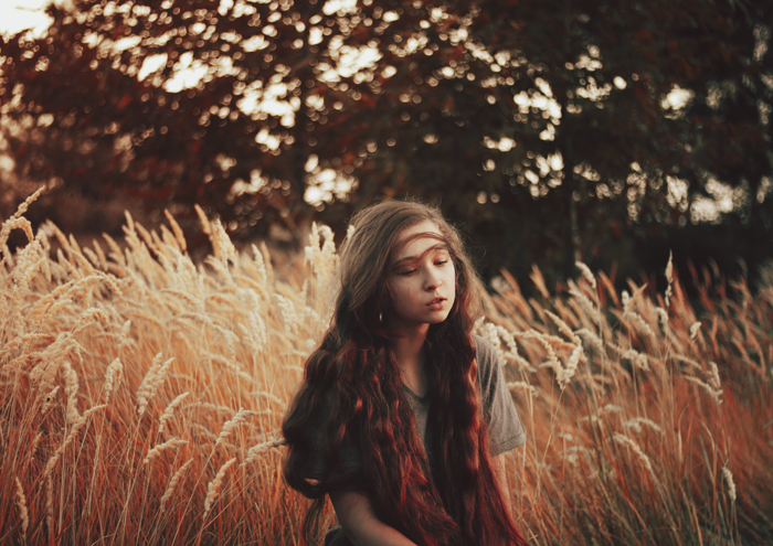 Dreamy portrait of a dark haired girl in a corn field with a blurry forest background.