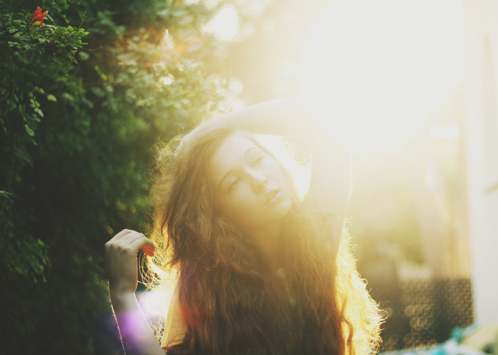 Dreamy light filled portrait of a dark haired girl with a blurry forest background.