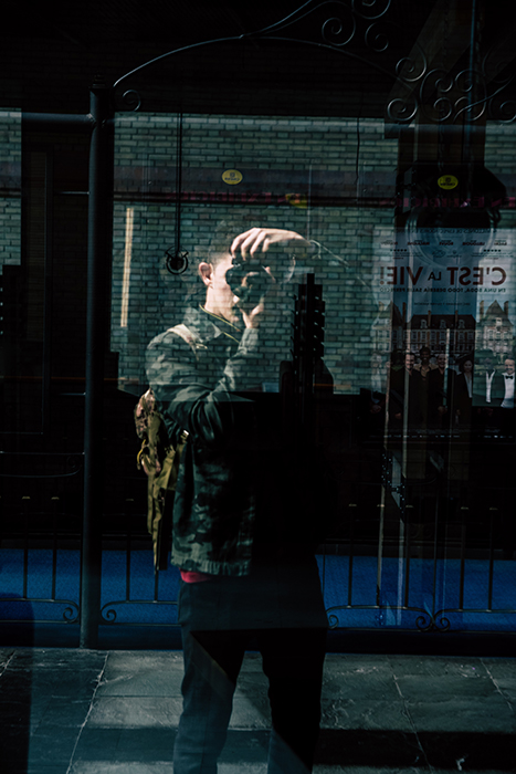 Photography of a person taking a photograph reflected in a shop window. Self portrait photography tips.