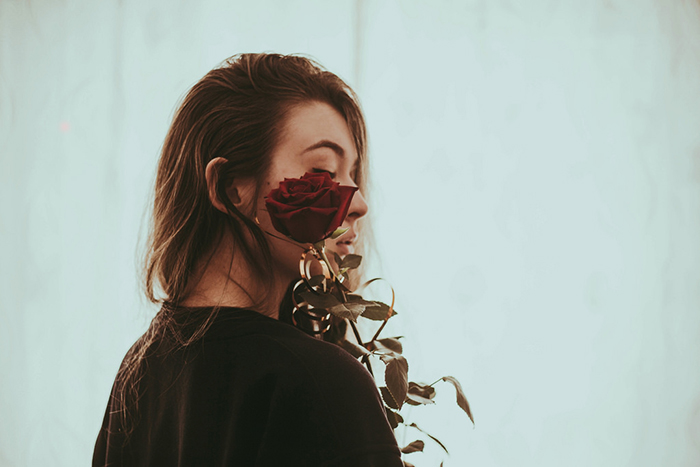Portrait photography of a girl holding a rose by her face. Self portrait photography tips.
