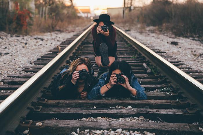 Photoof three girls on train tracks holding cameras. Self portrait ideas