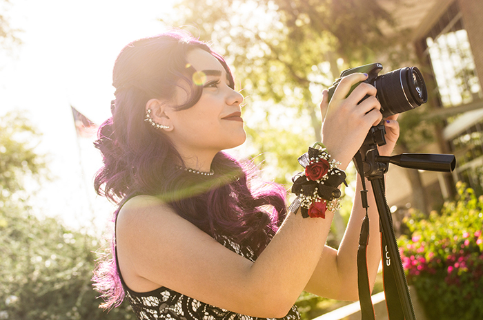 Bright and airy portrait of a girl holding a camera on a tripod. Self portrait ideas