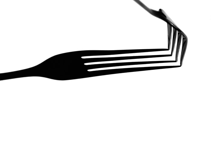 A black and white close up photograph of a fork with a strong shadow beneath. Combining light and shadow for abstract photography.