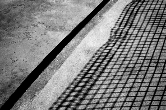 A shadowy black and white photograph of concrete with shadow of a fence. Combining light and shadow for abstract photography.