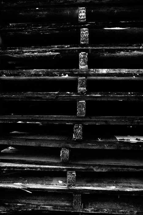 A shadowy black and white photograph of a stack of wooden palettes. Combining light and shadow for abstract photography.