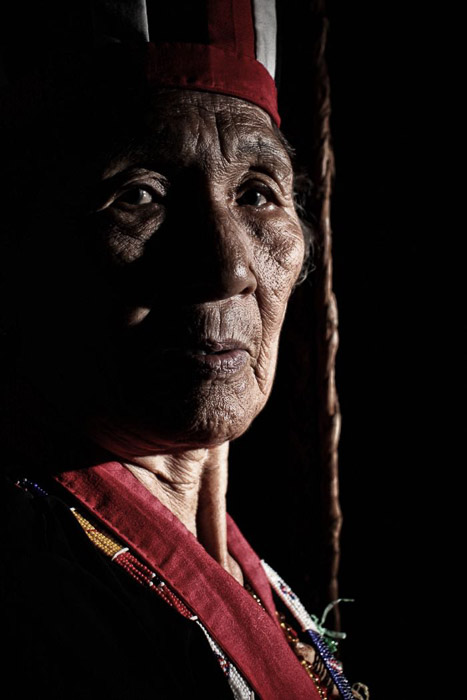Travel photography portrait of a tribal shaman in Borneo. Street photography accessories.