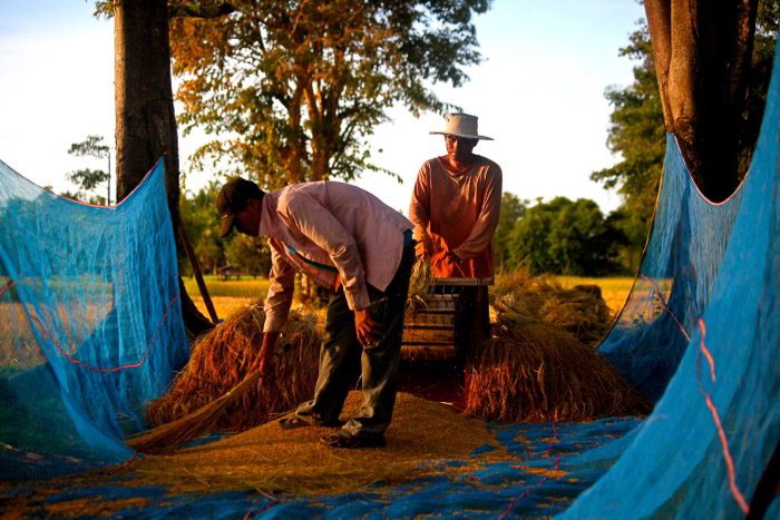 Travel photography of two farmers working in Laos. Street photography accessories.