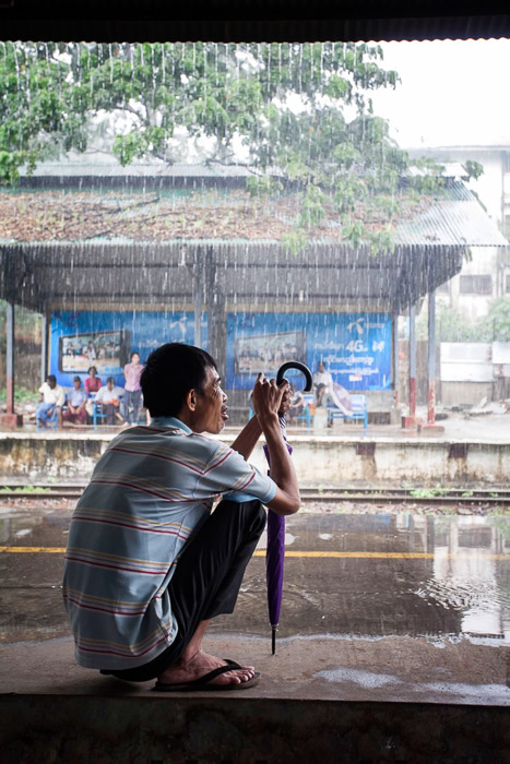 Travel photography of a man with umbrella taking shelter from tropical rain shower. Street photography accessories.
