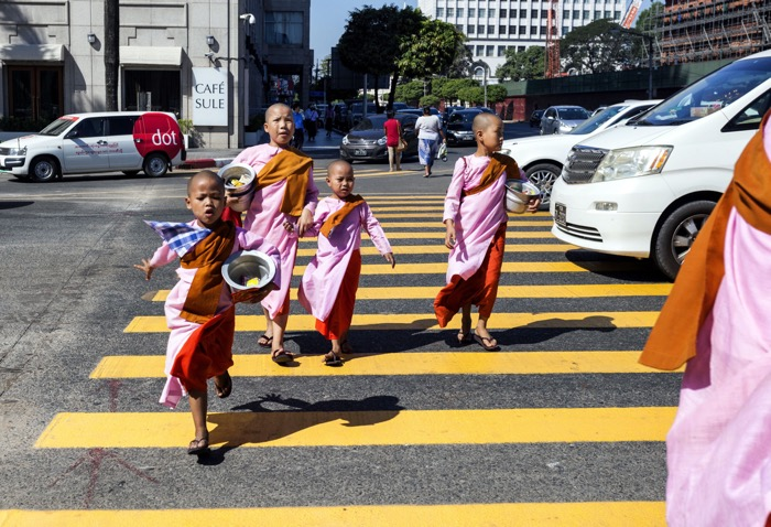 A group of children in traditional clothing crossing a busy street - street photography