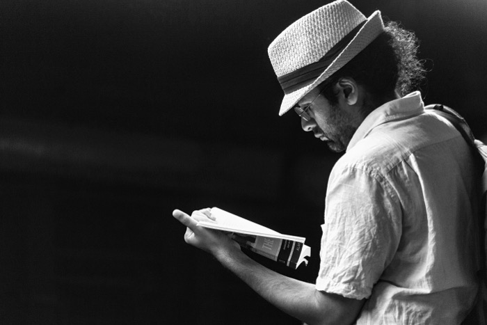Black and white candid photograph of a man in a white hat and shirt reading a book