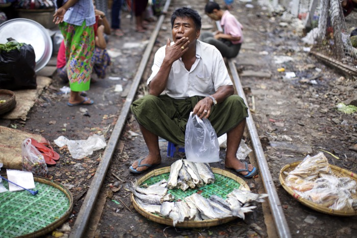 fish market scene, a man sits between train tracks with a basket of fish in front of him. street photography
