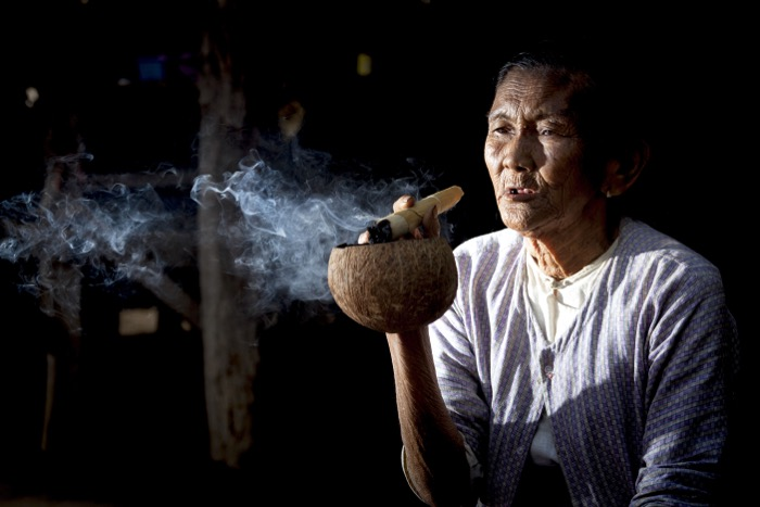 Street photograph of an old woman smoking a large cigar and using a coconut shell as an ashtray