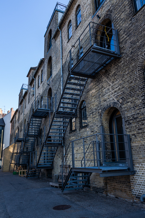 A small alley with side view of a brick building in Copenhagen.