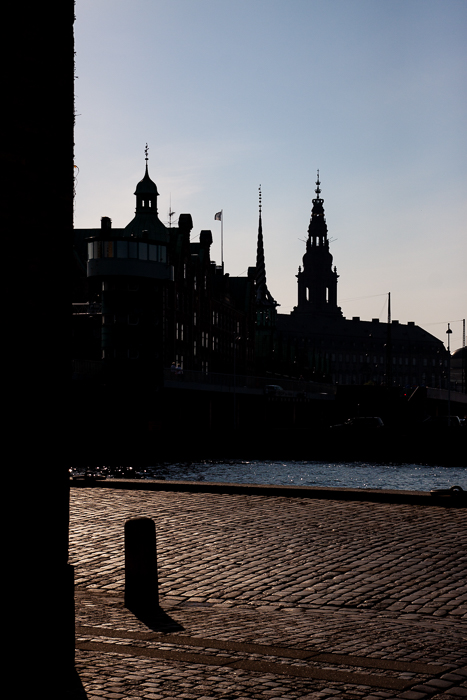 silhouettes of buildings against the bright sky, in the background of shadowy street and river in Copenhagen