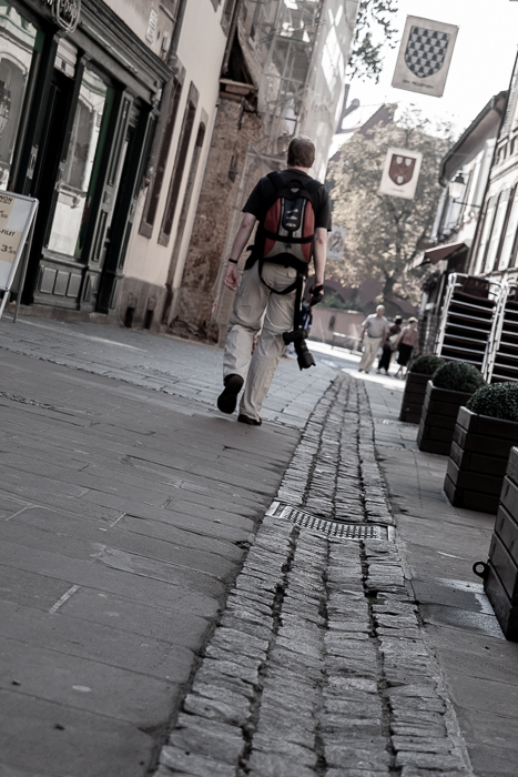 low angle view of a man walking away from the camera in the streets of Strassbourg. Urban photography