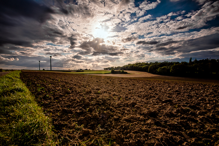 A dramatic cloudy sky over a peaceful countryside landscape. What is HDR photography?