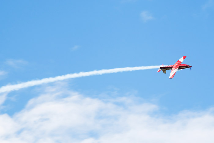 An airshow photography shot of a red airplane flying with a stream of contrails behind